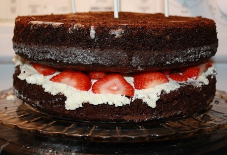 Sliced strawberries and whipped cream fill this chocolate cake...